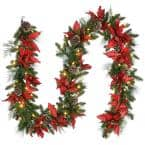 9 ft. Decorative Collection Feel Real Garland with Red Poinsettia, Gold Edged Cones, Flocked Cedar and 100 Clear Lights